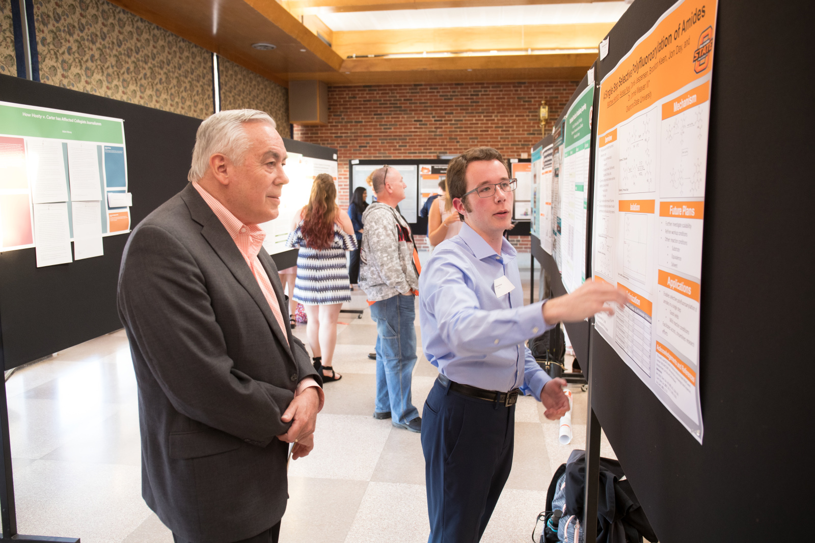 Dr. Sandefur engages with freshman research presenter at symposium